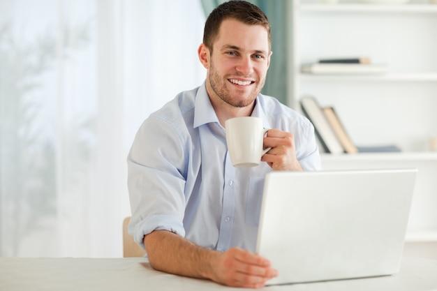 Empresário sorridente com uma xícara de chá