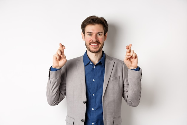 Empresário sorridente e esperançoso parecendo otimista, cruze os dedos, boa sorte