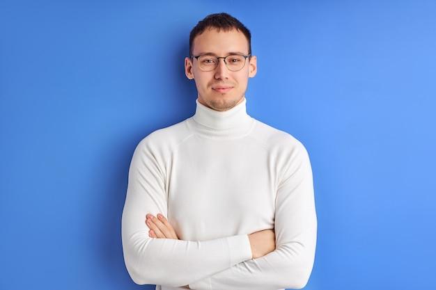 Empresário sorridente em óculos posando olhando para a câmera com os braços cruzados, vestindo uma camisa branca casual, isolado no fundo azul do estúdio