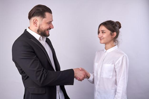 Empresário sorridente em um aperto de mão com uma empresária isolada no branco