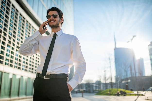 Empresário sorridente, falando ao telefone