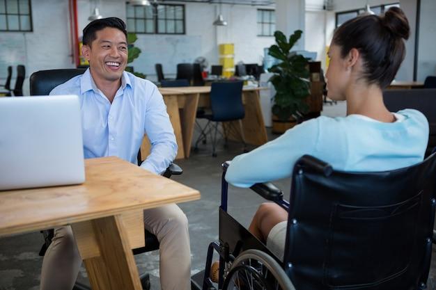 Empresário sorridente interagindo com colega com deficiência
