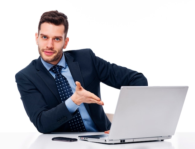 Empresário sorridente mostrando no laptop