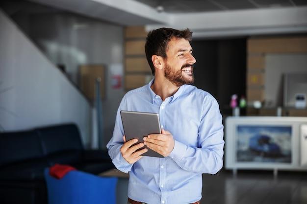 Empresário sorridente no saguão da empresa de exportação e usando o tablet.