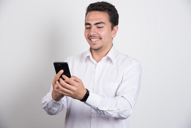 Empresário sorridente, olhando para o telefone em fundo branco.