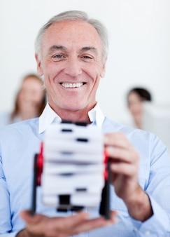 Empresário sorridente que consulta um titular de cartão de visita