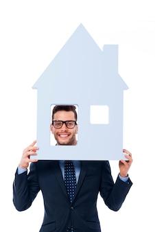 Empresário sorridente segurando a placa da casa