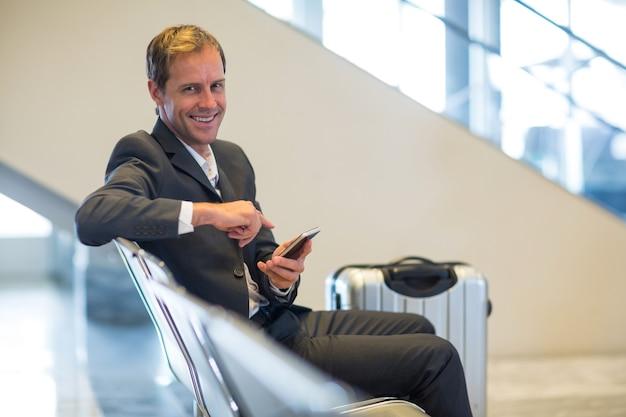 Empresário sorridente sentado com um telefone celular na sala de espera