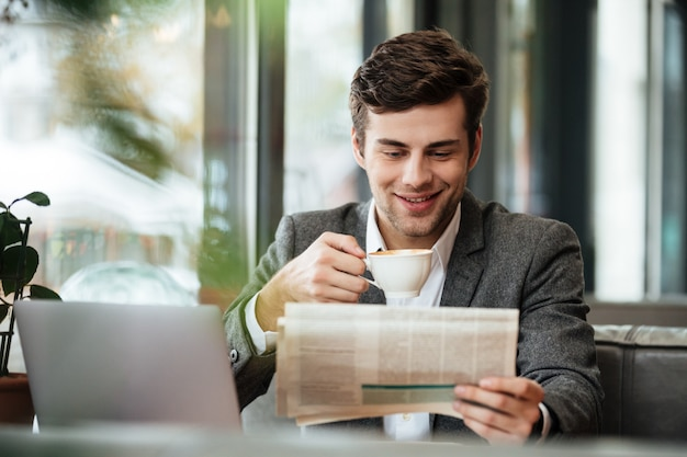 Empresário sorridente, sentado junto à mesa no café com o computador portátil enquanto lê o jornal e bebe café