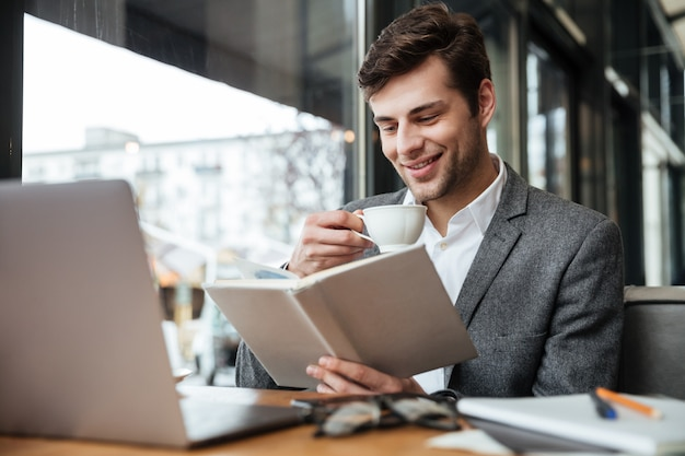 Empresário sorridente, sentado junto à mesa no café com o computador portátil enquanto lê o livro e bebe café