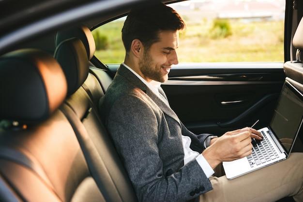 Empresário sorridente usando cartão de crédito plástico