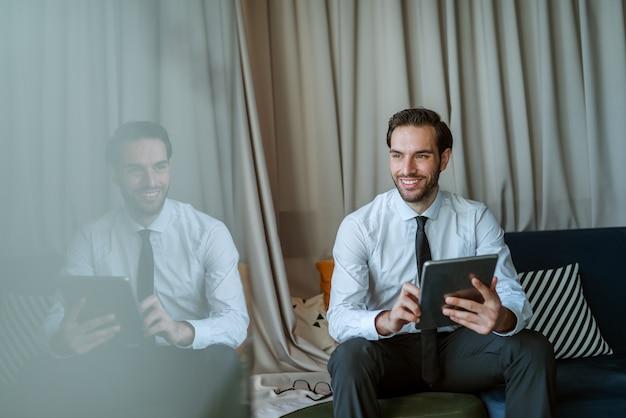 Empresário sorridente usando o tablet.