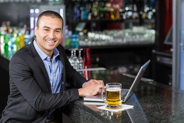 Empresário sorridente usando seu laptop