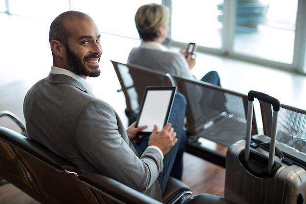 Empresário sorridente usando tablet digital na sala de espera