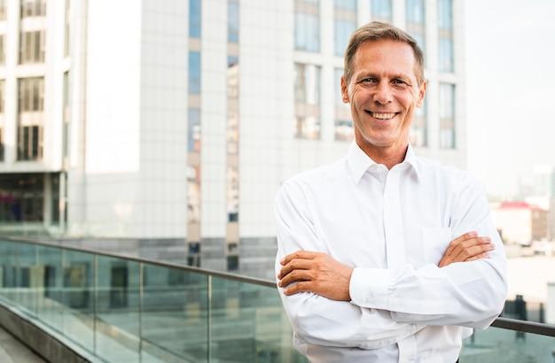Empresário sorrindo com os braços cruzados