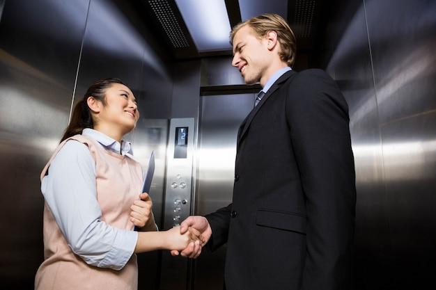 Empresário, sorrindo e apertando as mãos com a empresária no elevador