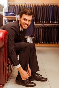 Empresário sorrindo e experimentando sapatos clássicos.