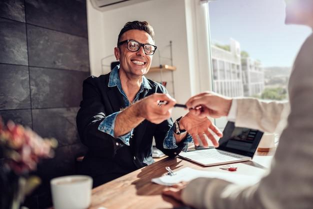 Empresário, sorrindo e passando a caneta para seu cliente