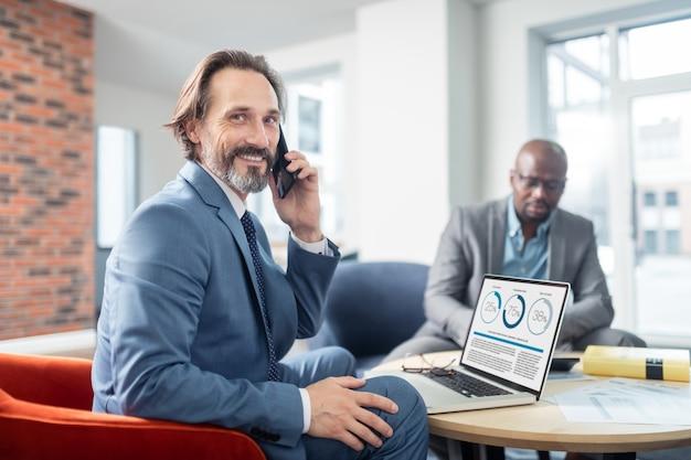 Empresário sorrindo. empresário de cabelos grisalhos e barbudo sorrindo ao receber uma ligação de um colega