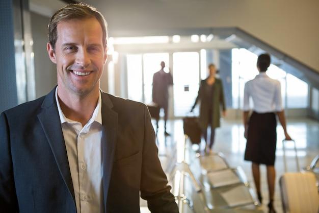 Empresário sorrindo no terminal do aeroporto