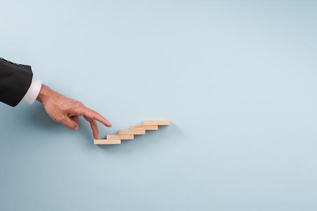 Empresário subindo as escadas com os dedos em uma imagem conceitual.