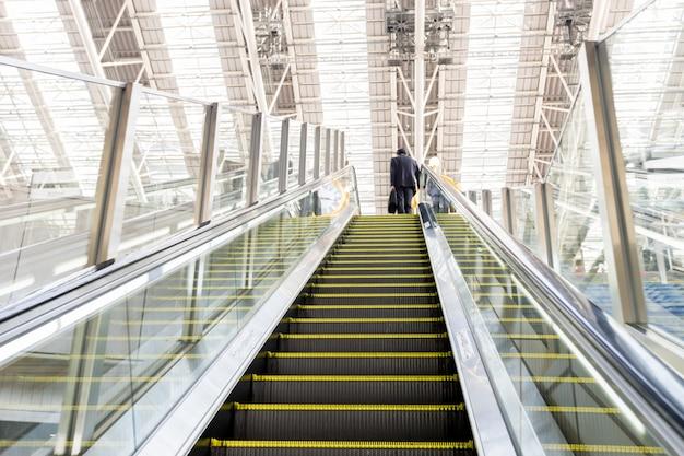 Empresário subindo uma escada rolante com bagagem