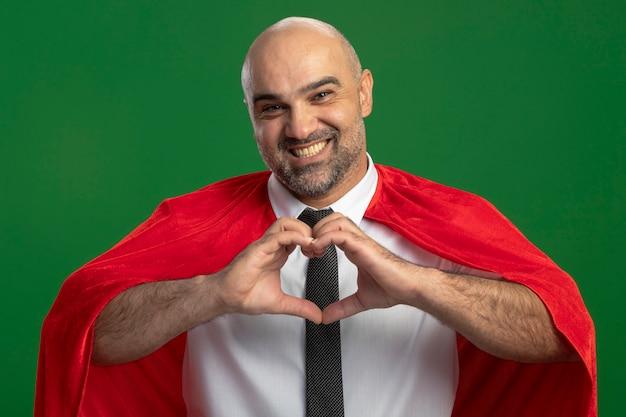 Empresário super-herói com capa vermelha fazendo um gesto de coração com os dedos olhando para a frente sorrindo alegremente em pé sobre a parede verde