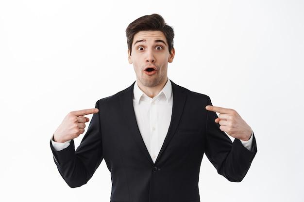Empresário surpreso de terno preto ofegante, apontando para si mesmo com rosto surpreso, sendo escolhido, em pé sobre uma parede branca