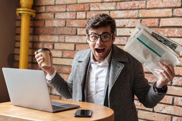 Empresário surpreso em óculos, sentado junto à mesa