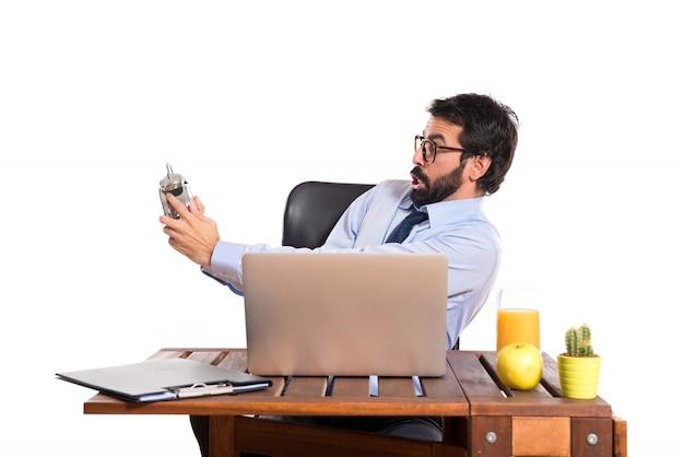 Empresário surpreso em seu escritório segurando um relógio