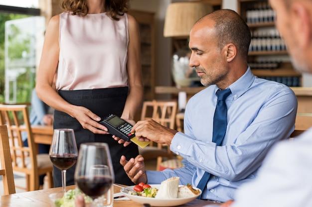 Empresário swiping cartão de crédito
