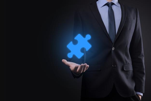 Empresário tem uma peça do quebra-cabeça nas mãos. o conceito de cooperação, trabalho em equipe, ajuda e suporte nos negócios.