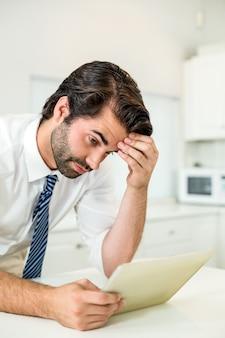 Empresário tenso olhando para tablet digital por tabela