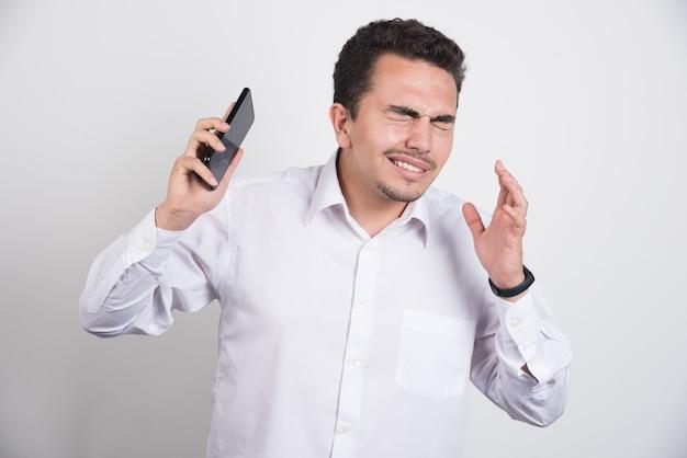 Empresário tentando fugir do telefone em fundo branco.