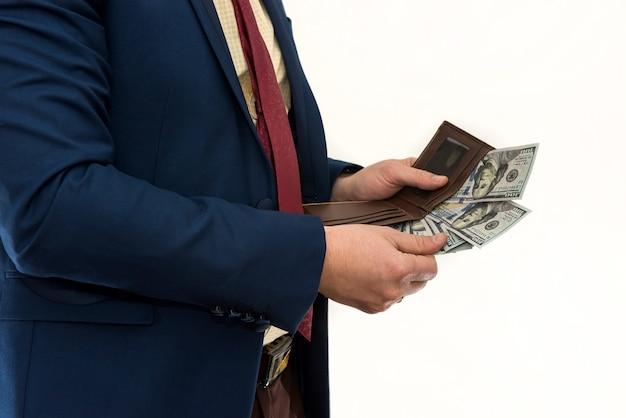 Empresário tira nota de 100 dólares de sua carteira para fazer uma compra ou aluguel