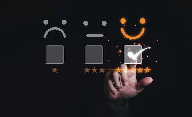 Empresário tocando e fazendo a marca para selecionar o rosto sorridente com cinco estrelas amarelas em fundo preto, a melhor satisfação do cliente e avaliação de produto e serviço de boa qualidade.