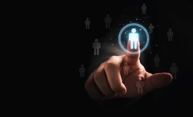 Empresário tocando o ícone humano virtual para o grupo de clientes em foco ou o conceito de recrutamento e desenvolvimento humano.
