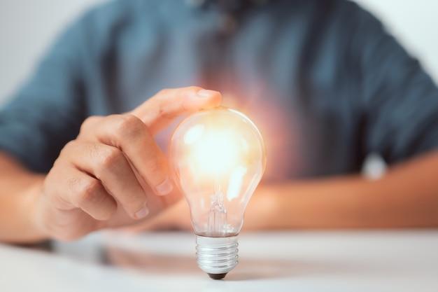 Empresário tocando uma lâmpada brilhante conceito de ideias para apresentar inovações