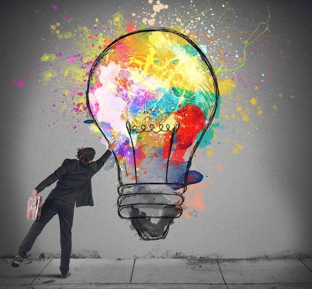 Empresário tocando uma lâmpada colorida