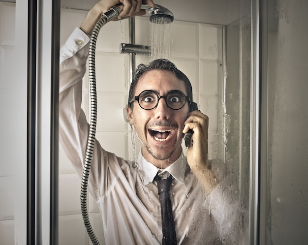 Empresário tomando banho com um telefone celular