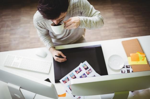 Empresário tomando café enquanto estiver usando a mesa digitalizadora