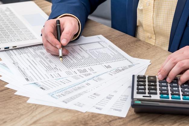 Empresário trabalha com formulário fiscal 1.040, laptop e calculadora