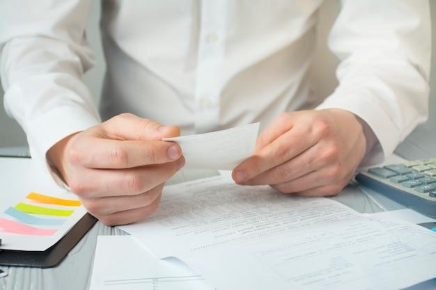Empresário trabalha com papéis. close-up das mãos de um homem que trabalha. trabalhe com cheques, impostos e contas. chuva de ideias. objetivos de negócios