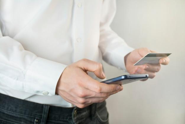 Empresário trabalha com um smartphone e um cartão de banco. close-up das mãos de um homem que trabalha. transferência de dinheiro. chuva de ideias. objetivos de negócios.