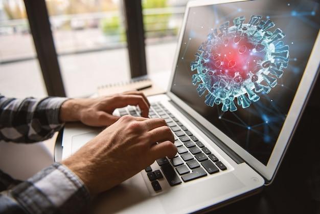 Empresário trabalha no escritório com um laptop e pesquisa notícias sobre o coronavírus covid-19.