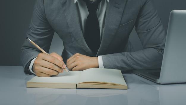 Empresário trabalha segurando uma caneta em um caderno no escritório