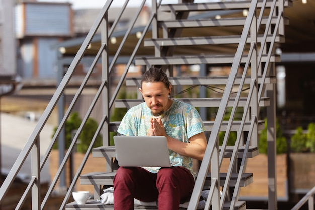 Empresário, trabalhando ao ar livre com o laptop, olhando na tela do computador