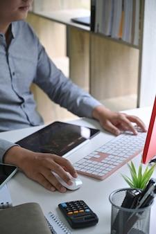 Empresário trabalhando com computador e analisando o investimento no mercado de ações no escritório.