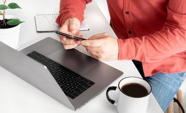 Empresário, trabalhando com computador remotamente ou se comunicando na rede social, sentado na cozinha em casa