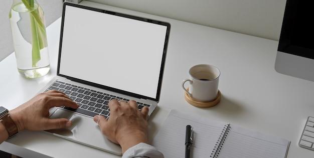 Empresário, trabalhando com o laptop na mesa de escritório branco com livro de agenda em branco, xícara de café e computador